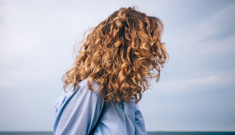 Side view female's head on blue sea background